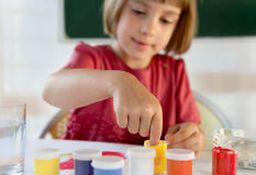 Schoolchild painting with hands Stock Image