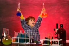 Schoolchild. School chemistry lessons. Happy little scientist making experiment with test tube. Happy smiling pupil. Drawing at the desk. Back to school and stock images