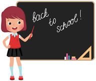 Schoolchild standing at the blackboard. Girl in school uniform standing at the blackboard Stock Photos