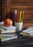 Schoolchild and student studies accessories. Books, notebooks, notepads, colored pencils, pens, rulers and a fresh red apple. Home. Made baby desktop. The royalty free stock image