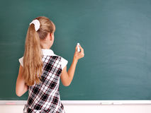 Schoolchild writing on blackboard. Royalty Free Stock Image