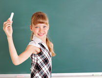 Schoolchild writing on blackboard. Stock Photo