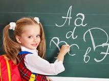 Schoolchild writting on blackboard. In schoolroom Stock Image