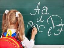 Schoolchild writting on blackboard Royalty Free Stock Images