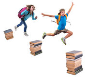 Schoolchildren with backpacks leaping over piles of books Stock Photo