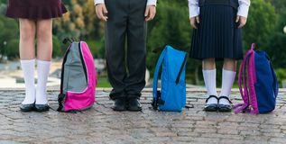 Schoolchildren with backpacks stand in the park ready to go to school. Long photo Stock Photos