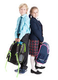 Schoolchildren with bags standing back to back full length, isolated white background Stock Photography
