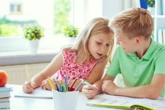 Schoolchildren are came back to school and learning at the table in classroom royalty free stock image