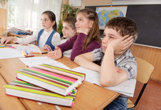 Schoolchildren at classroom during a lesson Stock Images
