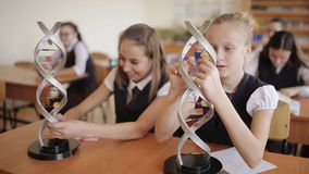 Schoolchildren in the classroom in the lesson learn dna layout. Schoolchildren in school uniform are studying the layout of dna sitting in the classroom. The stock video footage