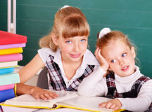 Schoolchildren in classroom near blackboard. Stock Photos