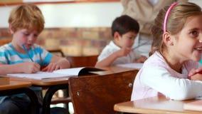 Schoolchildren colouring in books in classroom. In elementary school stock footage