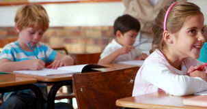 Schoolchildren colouring in books in classroom. In elementary school stock video footage