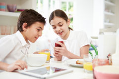 Schoolchildren With Digital Tablet And Mobile At Breakfast Stock Photo