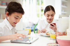 Schoolchildren With Digital Tablet And Mobile At Breakfast Stock Images
