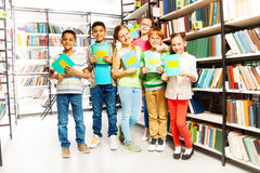 Schoolchildren with exercise books in library Stock Photos
