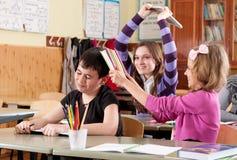 Schoolchildren fighting with books Stock Photography
