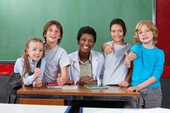Schoolchildren Gesturing Thumbs Up. Portrait of schoolchildren gesturing thumbs up with teacher at desk in classroom Stock Photos