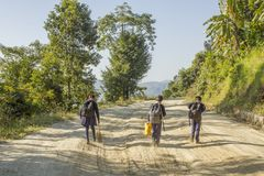 A schoolchildren girl and boys go to school on a dirt road in the forest against the backdrop of the mountains royalty free stock images