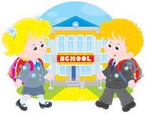 Schoolchildren going to school. Schoolgirl and schoolboy walking to school Stock Image