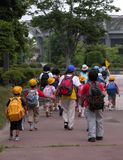 Schoolchildren group. Walking in a park together with their educators. Useful image to include it in a Back to school design Stock Photos