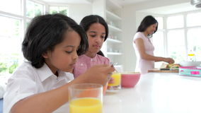 Schoolchildren Having Breakfast Whilst Mother Makes Lunch Royalty Free Stock Photo