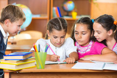 Schoolchildren having fun in classroom Royalty Free Stock Images