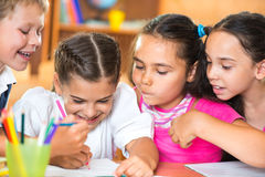 Schoolchildren having fun in classroom Stock Image