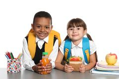 Schoolchildren with healthy food and backpacks sitting. At table on white background royalty free stock images