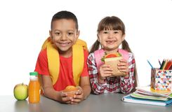 Schoolchildren with healthy food and backpacks sitting at table. On white background royalty free stock photos