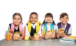 Schoolchildren with healthy food and backpacks sitting at table. On white background stock images