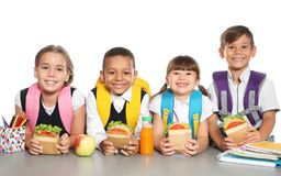 Schoolchildren with healthy food and backpacks sitting at table. On white background stock photos