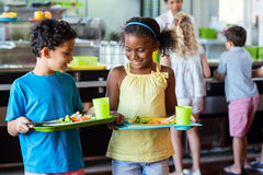 Schoolchildren holding food tray in canteen Stock Photo