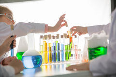 Schoolchildren in lab coats making experiment with test tubes. In chemical laboratory stock image