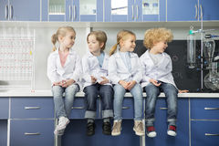 Schoolchildren in lab coats sitting together. In chemical laboratory stock photography