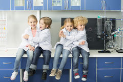 Schoolchildren in lab coats sitting together. In chemical laboratory royalty free stock photography