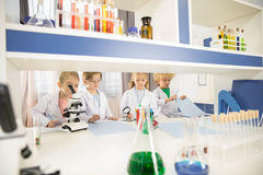 Schoolchildren in lab coats studying together. In chemical laboratory royalty free stock photos