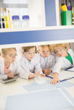 Schoolchildren in lab coats studying together. In chemical laboratory royalty free stock images