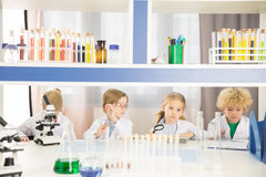 Schoolchildren in lab coats studying together Royalty Free Stock Photography