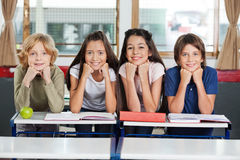 Schoolchildren Leaning At Desk Together Stock Photography