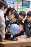 Schoolchildren looking at a globe in the classroom Stock Photo