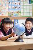 Schoolchildren looking at a globe in the classroom Stock Image