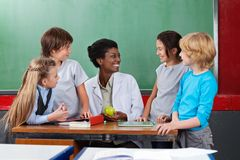 Schoolchildren Looking Teacher Sitting At Desk. Schoolchildren looking young African American teacher sitting at desk in classroom Stock Photo