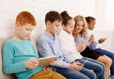 Schoolchildren with modern devices near brick wall. Children and technology. Kids with modern devices sitting near brick wall stock photo