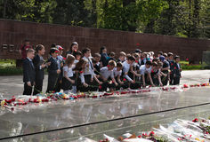 Schoolchildren put flowers to the eternal fire at the memorial Stock Image