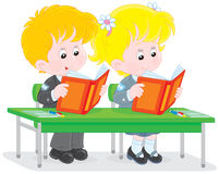 Schoolchildren read at a lesson. Schoolgirl and schoolboy reading books at their desk in a classroom Royalty Free Stock Photo