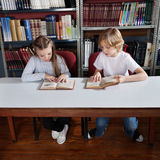 Schoolchildren Reading Book In Library Stock Photography