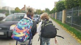 Schoolchildren run from school with backpacks. Happy childhood, Sorceresses, hooligans. stock video