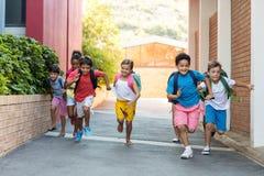 Schoolchildren running on footpath. Portrait of happy schoolchildren running on footpath royalty free stock photography