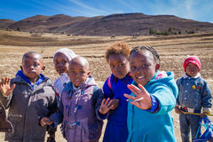Schoolchildren in rural Lesotho. LERIBE, LESOTHO - AUGUST 10, 2016: Friendly children walk home from school in beautiful winter scenery of south Africa`s royalty free stock images